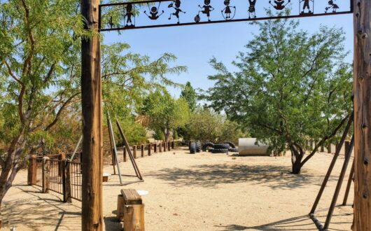 Then entrance to a simple, shaded kiddie park at Stagecoach Trails Campground. The ground is sandy surrounding some toys for children
