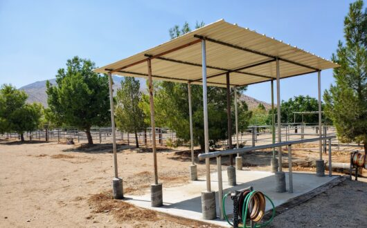 a wash rack for horses, with concrete floor, metal shade and hose to wash horses at stagecoach trails