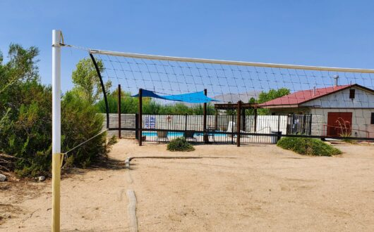 A sand volleyball court at stagecoach trails with the pool area in the background