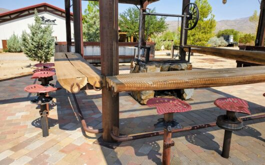 a Large log bbq area with bars and stools that groups can rent at Stagecoach Trails campground