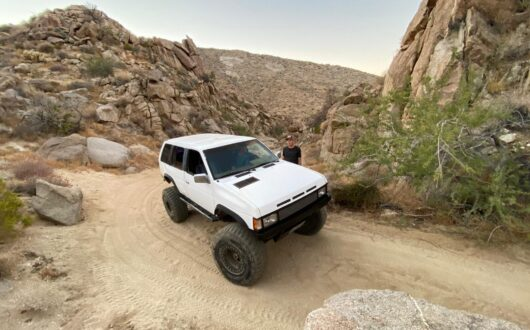 White Nissan Pathfinder turns on a desert road coming through a gap between two small rock covered hills