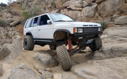 White Nissan pathfinder 4x4 crawling over rocks in the Anza Borrego desert near Stagecoach Trails Campground