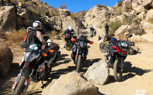 six dual sport motorcycles with riders taking pictures as they cruise through a desert canyon